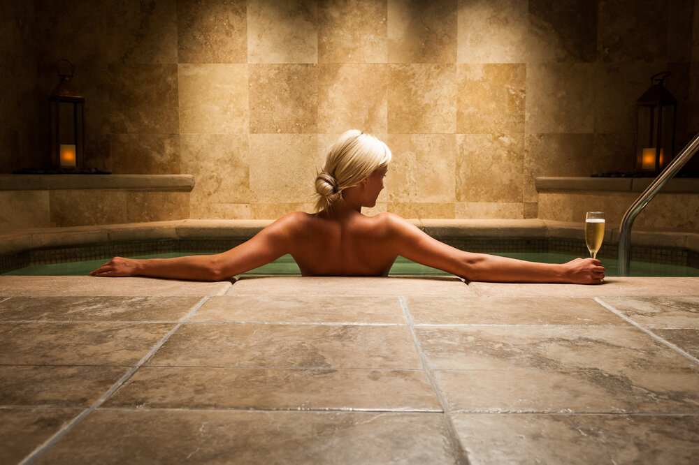 Woman in hot tub with glass of champagne